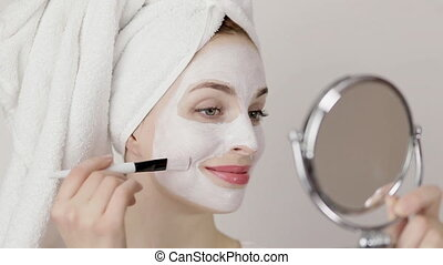 Face peeling mask, spa beauty treatment, skincare. Pretty Caucasian girl applying white facial mask on her face with brush, looking at the mirror. Isolated on white, close-up.