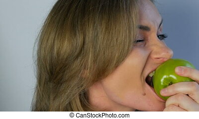 Face portrait of a young beautiful woman with an appetite and funny eating a big green apple, biting off pieces. Vegetarianism concept, fresh fruits in the hands of a young girl, healthy food.