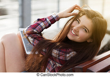 Face portrait of young woman using a tablet pc