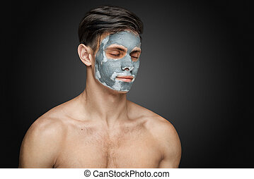Portrait of a beautiful young man with a facial clay mask, face and body skin care treatment.