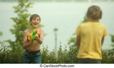 Two friends conducting a game battle with water pistols