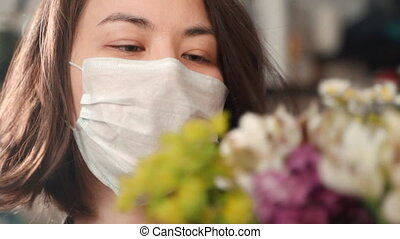 Face view of female florist is working with flowers in creative workshop during quarantine.