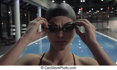 Face woman swimmer take off goggles in water swimming pool...