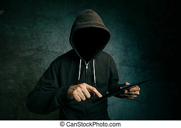 Faceless hooded unidentifiable male person using tablet computer