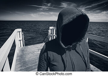 Faceless Hooded Unrecognizable Woman at Ocean Pier, Abduction Concept