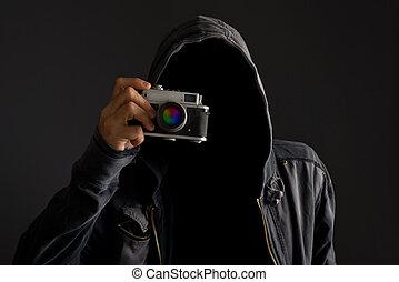 Faceless man with dusty camera