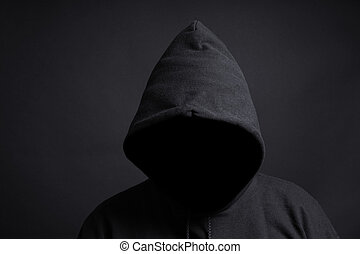 faceless person wearing black hoodie hiding face in shadow