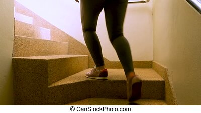 Faceless sportswoman in active wear going upstairs at home...