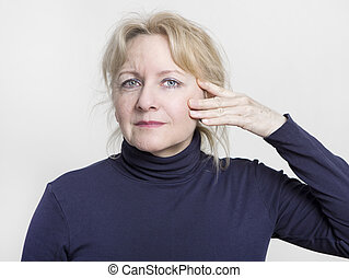 an older woman with a face half is lifted