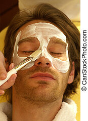Facemask - A man receives a facial treatment in the spa