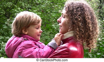 faces mother with girl in autumn park