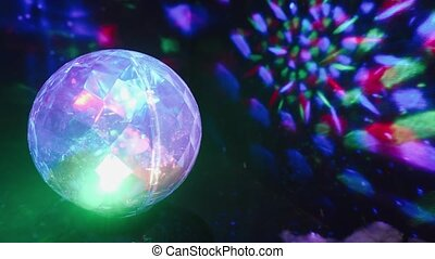 Faceted festive disco ball garland rotates in the dark. 4k.