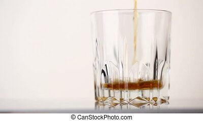 Faceted glass filled with whiskey and ice cubes - Faceted...