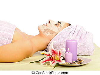 Beautiful woman at spa lying with clay mask on.