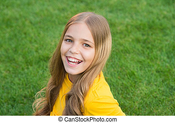 Facial care. kid beauty and fashion. teen girl after hairdresser. relax on green grass. spring leisure time. happy childhood. kid with stylish hair. cheerful smile. happy little girl has curly hair