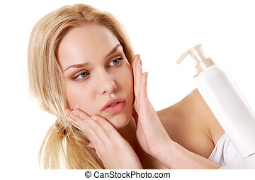 Portrait of pretty female touching her face while applying lotion