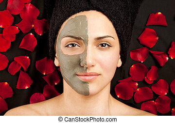 young beautiful woman having a clay mask on half of her face