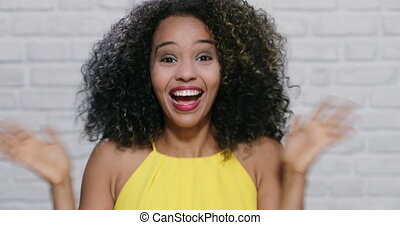 Portrait of excited black woman laughing against white wall as background. African Amercican girl looking at camera.