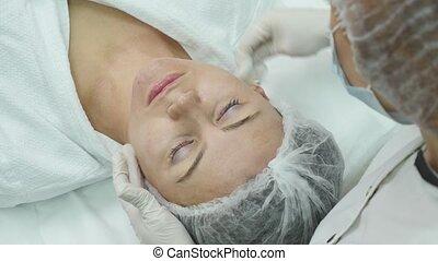 Facial mask applying using brush in Beauty salon. Spa...