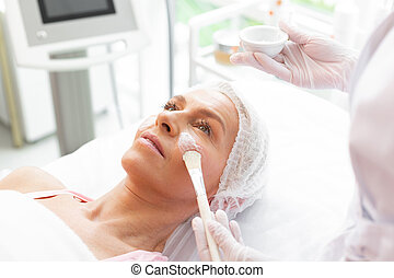 Nice aged woman having a facial mask applied