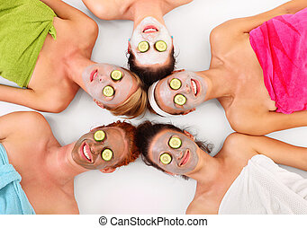 Facial masks - A picture of five girl friends relaxing with...