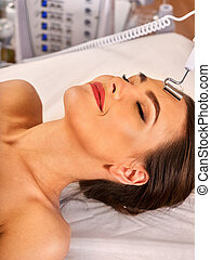 Facial massage at beauty salon. Electric stimulation skin care of woman. Professional equipment for microcurrent lift face. Anti aging rejuvenation and non surgical treatment.