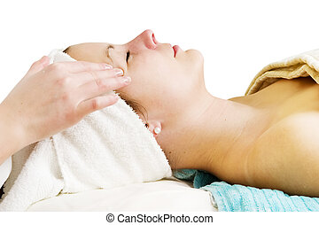 Facial Massage - A woman receiving a facial massage at a...