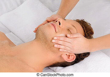 Facial massage. Top view of relaxed young men lying on the...