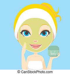 Blonde woman applying facial beauty skin care cream mask treatment