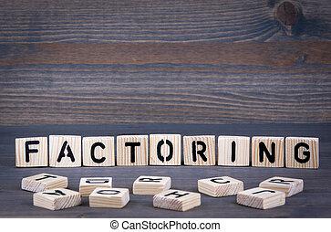Factoring word written on wood block. Dark wood background with texture