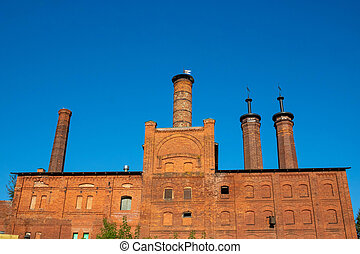 Factory brick chimneys on a red old building against a blue sky