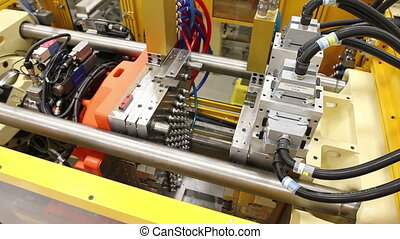 A wider shot cuts to a close-up of an injection molding machine in a factor