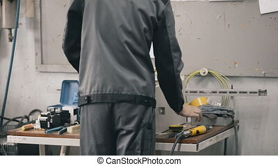 factory male technician install electrical steel cabinet all the components of electrical switchboards.