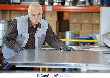 factory man worker holding metal sheet in workshop