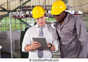 manager and worker looking at tablet computer - factory...