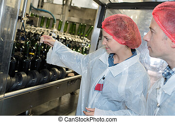 Factory operatives overseeing bottling plant production line