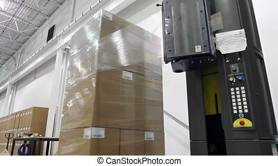 Factory Shrink Wrap 2 - A shrink wrap machine covers a large...