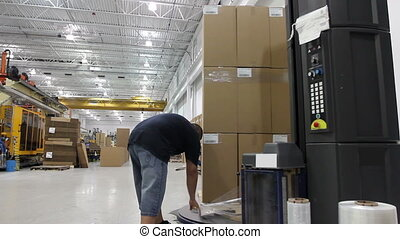 Factory Shrink Wrap - A worker starts a shrink wrap machine...