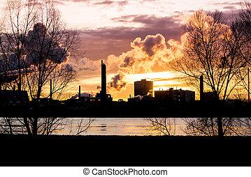 Factory with smokestacks at sunset