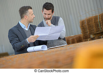 factory worker and boss checking a paper