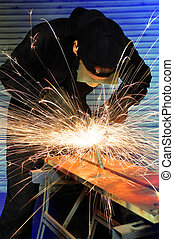 grinding metal - factory worker creating sparks whilst...