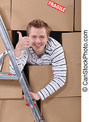 Factory worker emerging from cardboard boxes