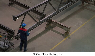 Factory worker in hard hat is moving a metal detail with a remote crane