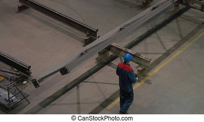Factory worker in hard hat is moving a metal detail with a...