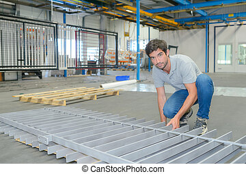 Factory worker manufacturing metal railing
