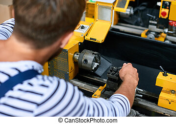 Factory Worker Operating Metalworking machine