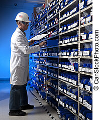 Factory Worker taking inventory in stock room of a manufacturing company