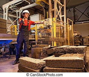 Factory worker throwing defective block