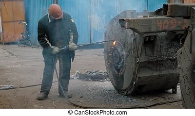 Factory worker using special welding while working with...