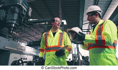 Factory worker warn coworker about safety and give hardhat to him